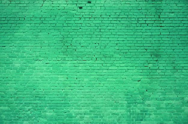 De textuur van de bakstenen muur van vele rijen bakstenen die in groene kleur worden geschilderd