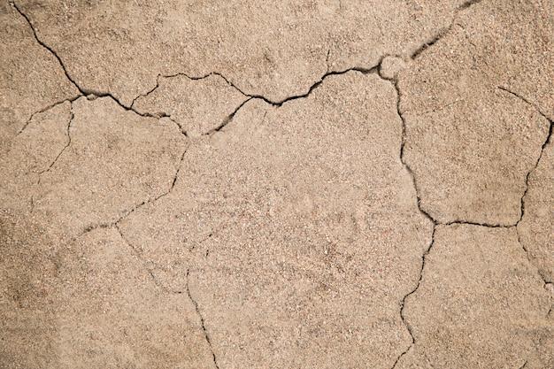 De textuur van de barst in de grond met zand in de vorm van bliksemclose-up. achtergrond gebarsten aarde
