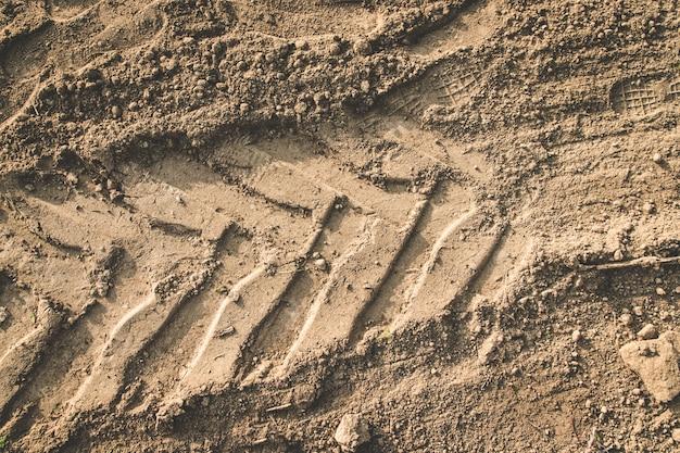 De textuur van de bruine aarde van de zandweg met sporen van het loopvlak van de autobanden van de tractor.