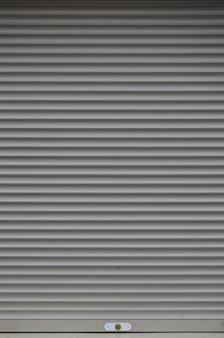 De textuur van de deur of het raam van de sluiter in de lichtgrijze kleur