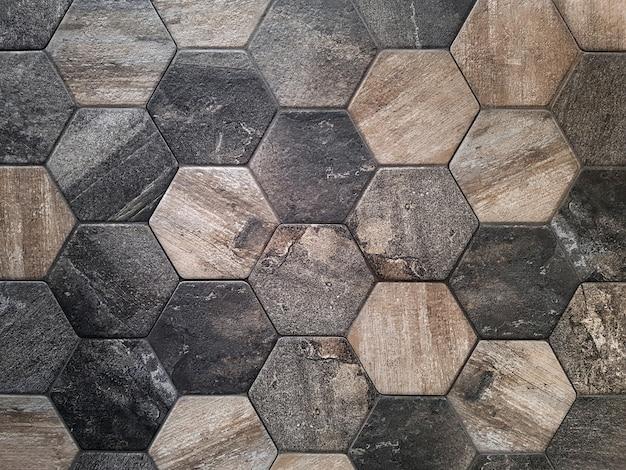 De textuur van de keramische tegels in de vorm van een zeshoek gemaakt van bruine natuursteen achtergrond