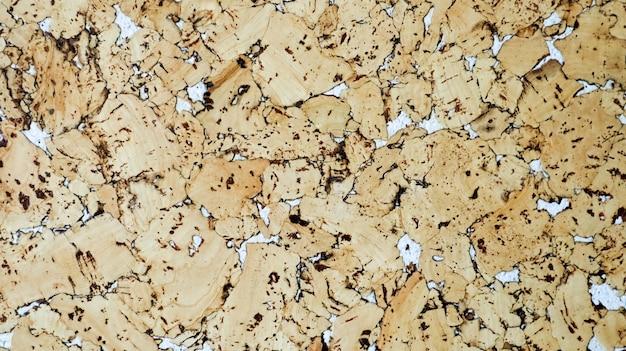 De textuur van de kurk. wandbekleding kurk witte accenten. cork board textuur achtergrond. decoratief kurkpaneel voor gevelbekleding. houten bruine achtergrond. houtstructuur, behang.