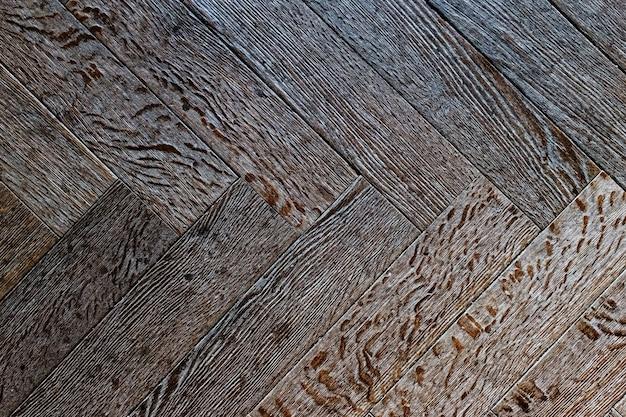 De textuur van de oude houten vloer, de diagonale opstelling van het parket.