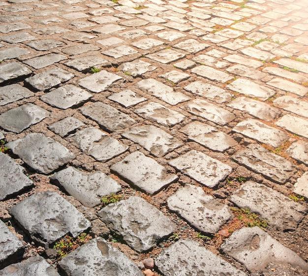De textuur van de steenbestrating met zonlicht