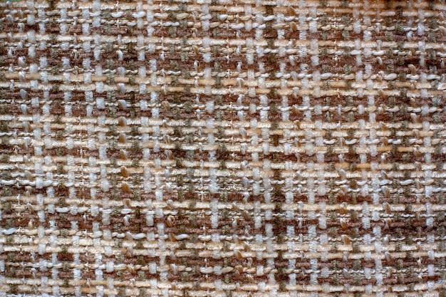 De textuur van de stof. kruis weven. wollige bruine en witte draden. ruimte kopiëren.