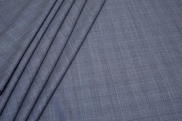 De textuur van de wollen stof in een grijze kooi.
