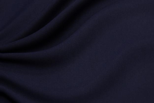 De textuur van de wollen stof is donkerblauw. achtergrond, patroon, gebreide kleding.