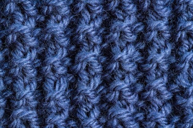 De textuur van een blauw gebreid garen. gebreide en winterkleding