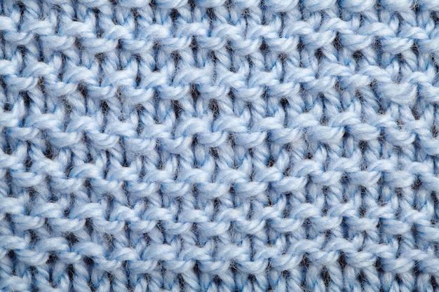 De textuur van een blauwe gebreide wollen stof