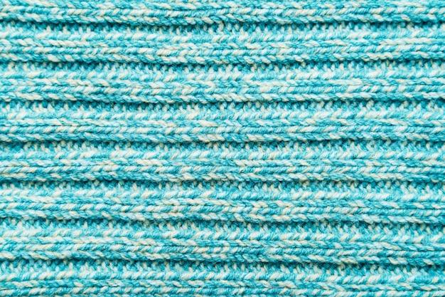 De textuur van een blauwe turquoise gebreide stof. sweater achtergrond