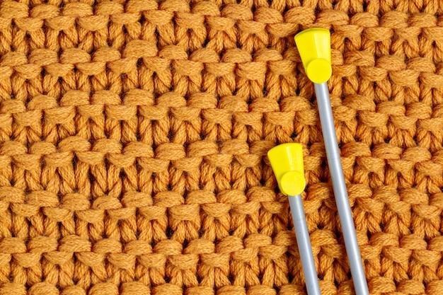 De textuur van een geel gebreid garen en breinaalden. gebreide en winterkleren. kopieer ruimte