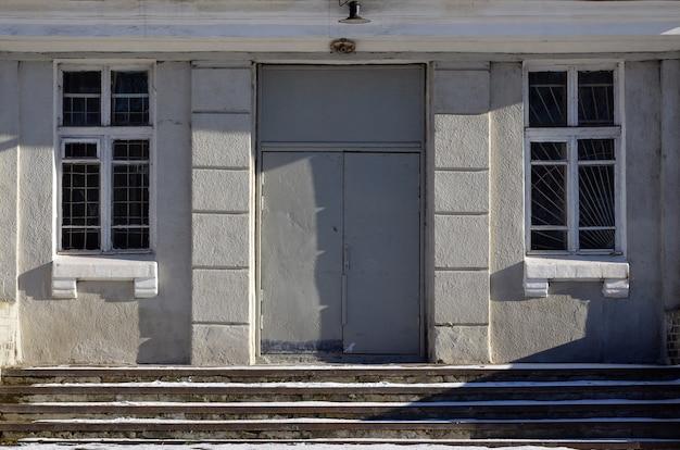 De textuur van een geschilderde metalen deur van een betonnen muur