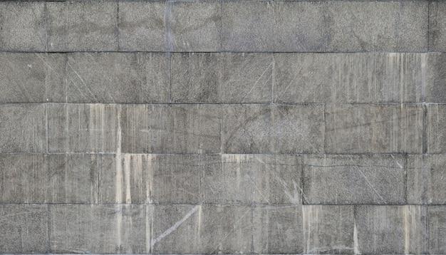 De textuur van een muur van grote graniettegels die worden behandeld