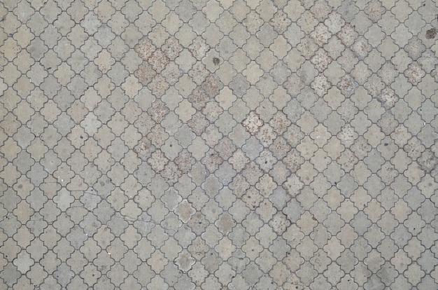 De textuur van een ritmisch mozaïek gemaakt van betontegels