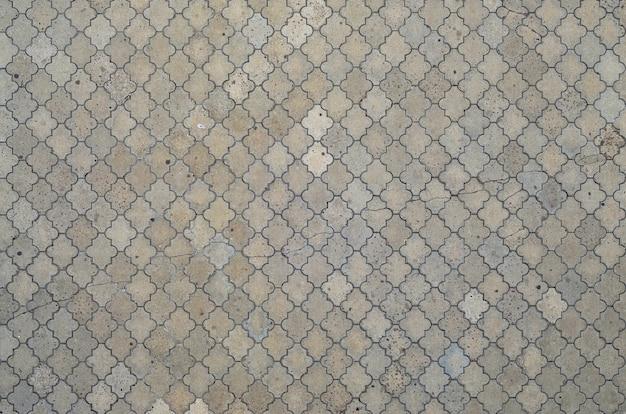 De textuur van een ritmisch mozaïek gemaakt van betontegels.
