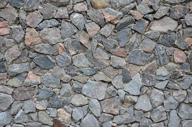 De textuur van een sterke stenen muur van veel betonnen stenen van verschillende vormen