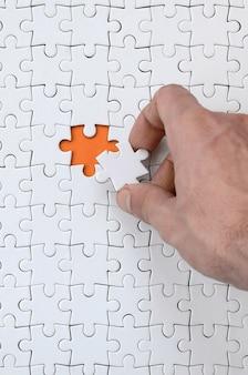 De textuur van een witte puzzel in de geassembleerde staat met één ontbrekend element dat de mannelijke hand erin legt