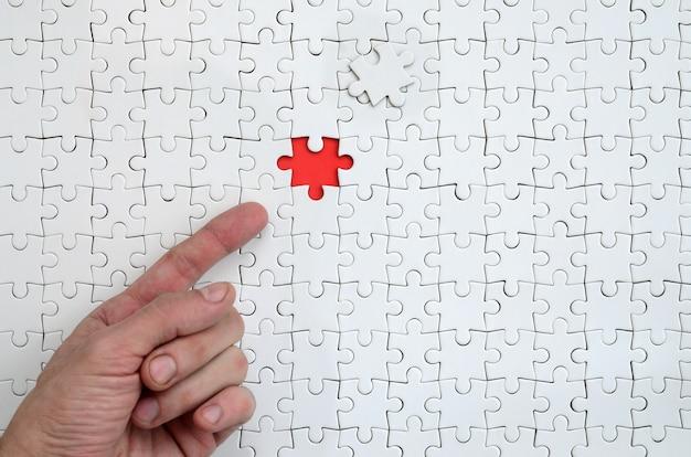 De textuur van een witte puzzel in de geassembleerde staat met één ontbrekend element