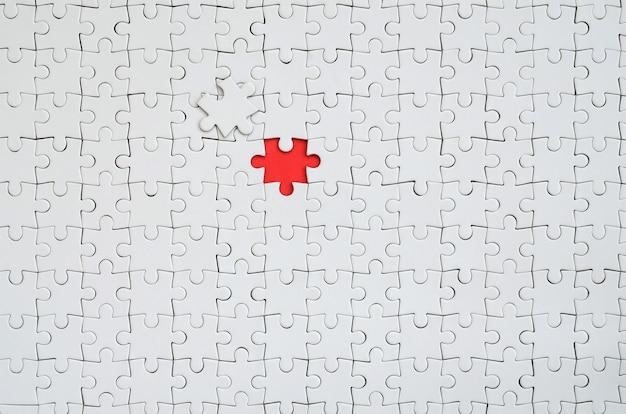 De textuur van een witte puzzel in een geassembleerde staat met een ontbrekend element dat een rode ruimte vormt