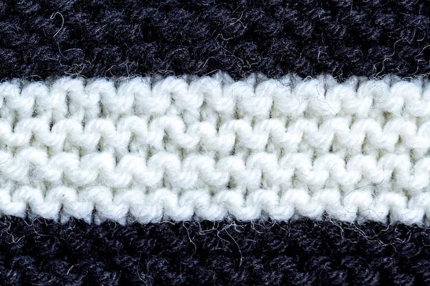 De textuur van een zwart en wit gebreid garen.
