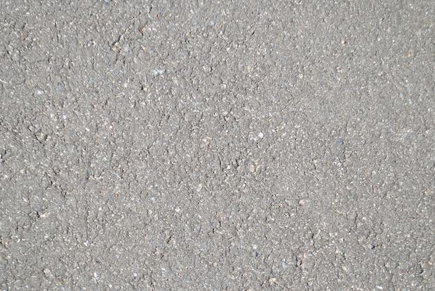 De textuur van het asfalt op de weg in een lichte schaduw verlicht door de zon voor het hele frame, grijs en grungy