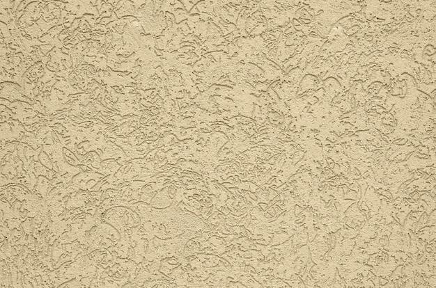 De textuur van het beige decoratieve gips in schorskeverstijl