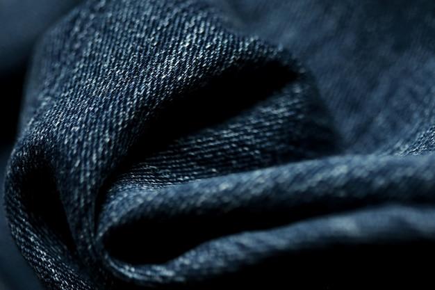 De textuur van het jeansdenim dichte omhooggaand, concentreert slechts één punt, zachte blured achtergrond