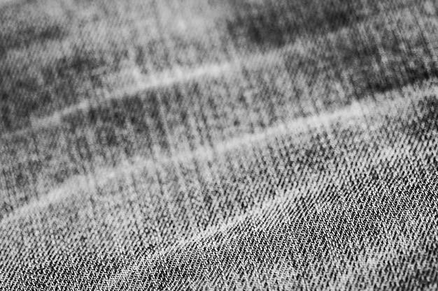 De textuur van het jeansdenim sluit omhoog, concentreert slechts één punt, zacht blured behang als achtergrond