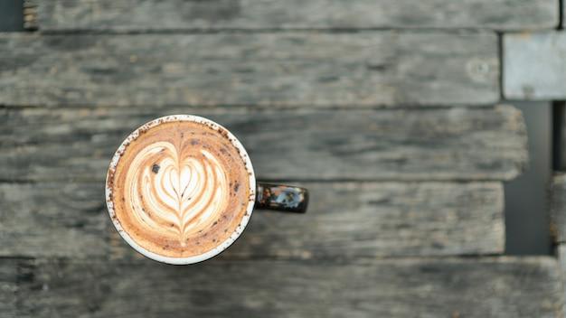 De textuur van het koffie latte hart op houten vloer.