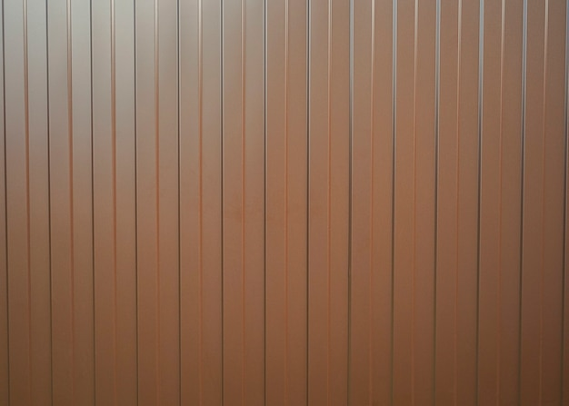 De textuur van het metalen hek van het bruine profiel met verticale lijnen