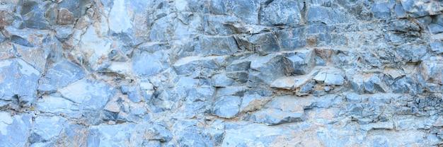 De textuur van het oppervlak van de grijsblauwe natuursteenrotsen als achtergrond. banner