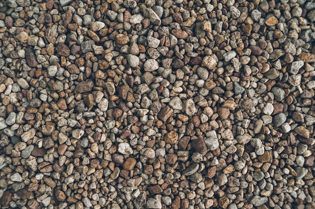 De textuur van kleine stenen, buitenshuis kust.