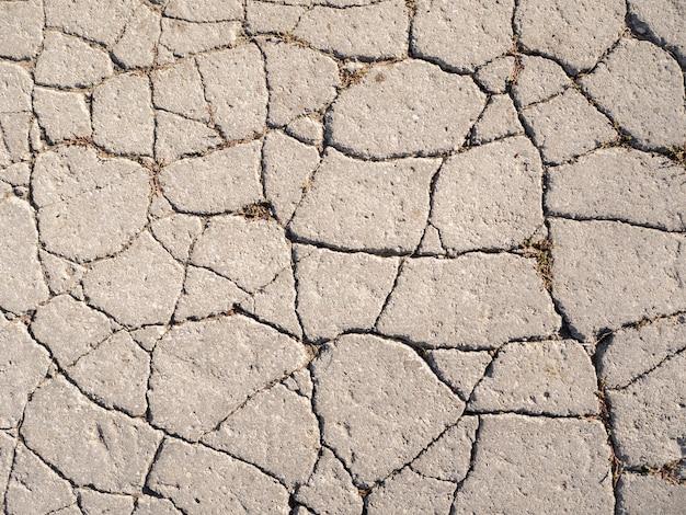 De textuur van oud asfalt met scheuren.