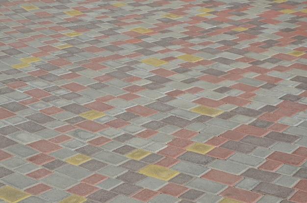 De textuur van straatstegen in de vorm van een mozaïek van bewerkte straatstenen in zonlicht