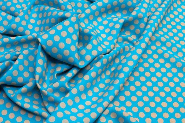 De textuur van zijde stof met witte erwten op blauw.