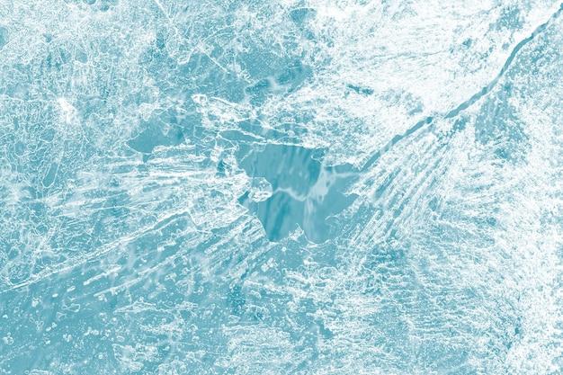 De textuurmacro van de ijsoppervlakte die op een blauw behang wordt geschoten