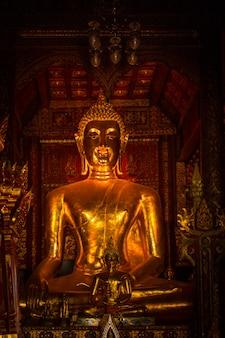 De thaise gouden de kunst volledige oude antiquiteit van boedha groeit in het donkere verticale schot
