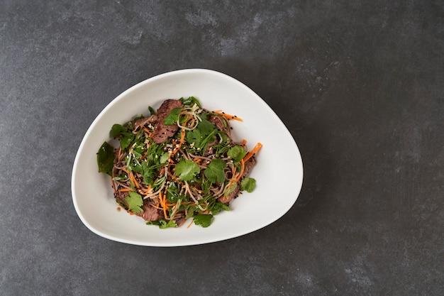 De thaise salade van stijl warme soba in witte kom op grijze lijstachtergrond