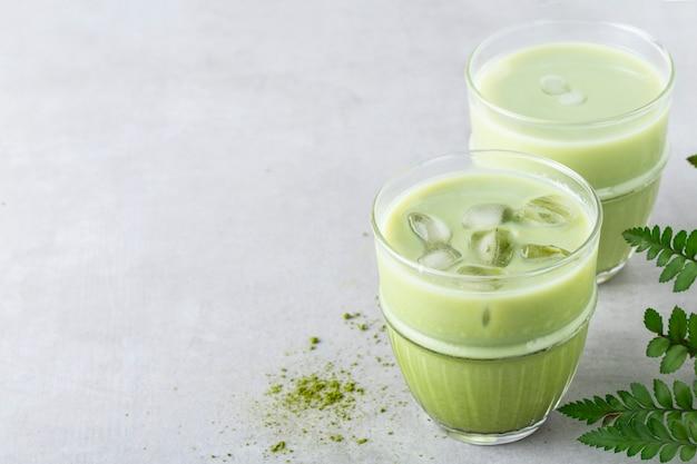 De thee van ijsmatcha met ijs en melk in een glas op een grijze achtergrond