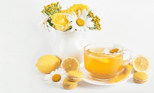 De theekop van madeliefjes met schijfje citroen en verse kamillebloemen in een vaas