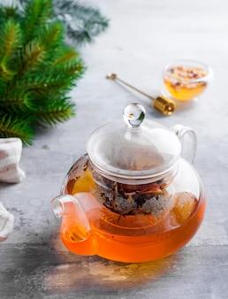 De theepot van het glas met bloemen bond thee, hete thee in glastheepot en honing met de stok van de metaalhoning