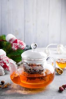 De theepot van het glas met bloemen bond thee, hete thee in glastheepot en honing