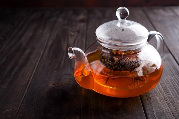 De theepot van het glas met vers gezet aftreksel dat op een houten bruine achtergrond wordt gebonden