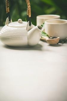 De theesamenstelling op tropische bladerenachtergrond, sluit omhoog