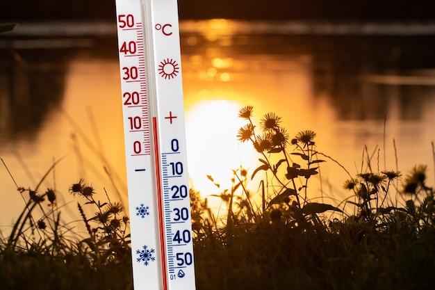 De thermometer op de achtergrond van de rivier in de herfst tijdens zonsondergang toont een temperatuur van 15 graden