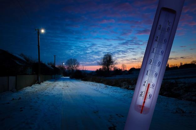 De thermometer op de achtergrond van het winterlandschap een temperatuur van min 17 graden