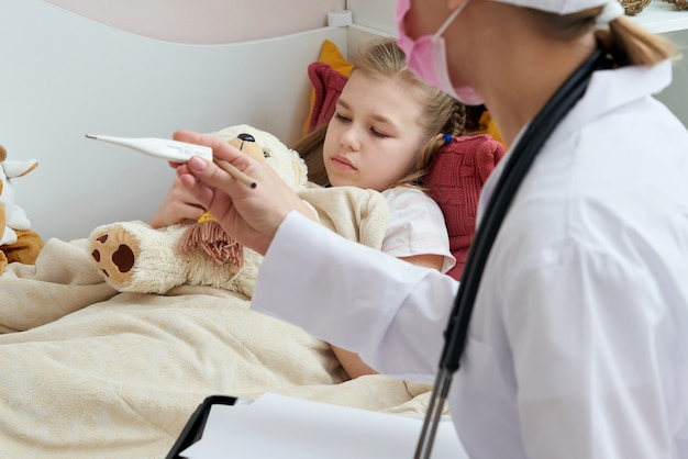 De thermometer van de artsenholding en het controleren van ziek meisje. ziek meisje op bed met koorts die temperatuur meten