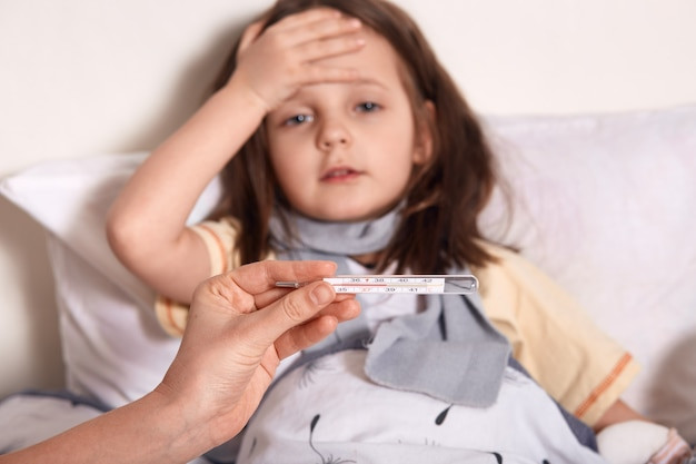 De thermometer van de moederholding in handen, ziek meisje die in bed liggen en haar palm op voorhoofd houden, die aan op hoge temperatuur lijden