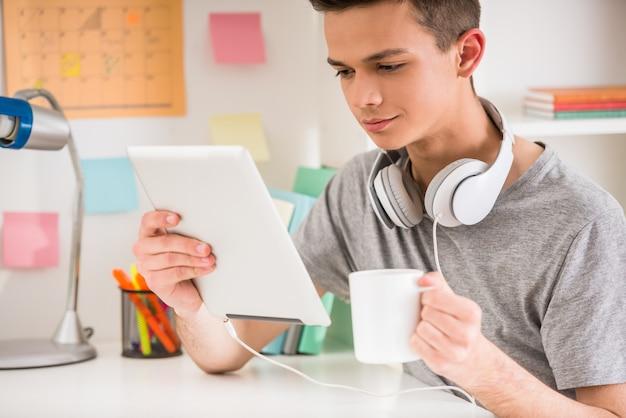 De tiener gebruikt tablet en drinkt thee.