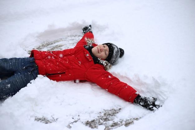 De tiener ligt in de sneeuw en maakt sneeuwengel